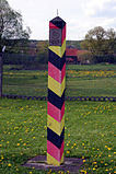 "A red/black/yellow striped square-shaped pole with a metal spike on the top side. A metal plaque with an emblem and the words ""Deutsche Demokratische Republik"" is visible on one face."