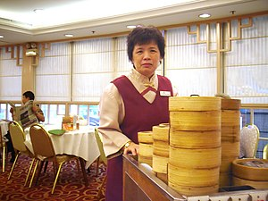 Yum cha - A woman serving dim sum from a cart in a Cantonese restaurant in Hong Kong