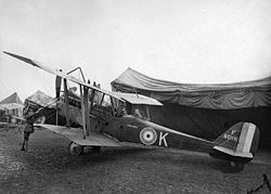 Single-engined military biplane with two men in the cockpit, parked in front of a large tent
