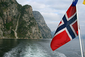 A fjord in Norway, with the Norwegian flag in ...