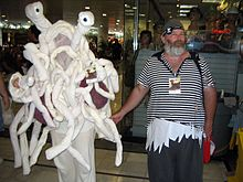 A man dressed in pirate regalia standing next to a person costumed as the Flying Spaghetti Monster.