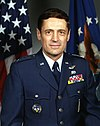 man in Air Force uniform, American flag in background