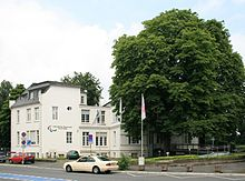 A white building with trees next to it fronting a street with a car driving past