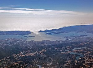 Golden Gate - San Francisco's natural air conditioning, the fog, rolls in through the Golden Gate, covering Alcatraz Island.