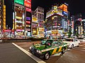 Green and yellow taxi at night in Yasukuni-dori Avenue, Shinjuku, Tokyo.jpg