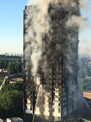 Grenfell Tower fire - Grenfell Tower in the early morning of 14 June. The burnt cladding is visible on the outside of the building.