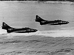 Grumman F9F-6 Cougars of VF-142 in a low-level flight over the coast of Guam, in January 1956 (NNAM.1996.253.7411.033).jpg