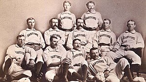 In this photograph of a baseball team, eleven men are situated in three rows facing the camera, with four sitting on the floor, five sitting in chairs, and two standing.