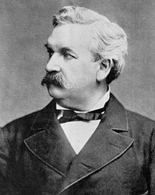 A monochrome photograph of a man from the chest up, approximately 50 years old, with a large moustache and no sideburns, a full head of white hair, looking sharply to the left
