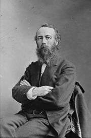 A white man with a scraggly beard and wearing a suit, sitting in a chair with his arms crossed.
