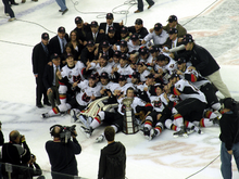 About 30 people gather around a trophy in celebration, many of them raising a single finger.