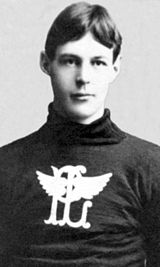 "Black and white image of a young man shown from torso up, with arms cropped out of image. Wearing wool sweater with an image, a ""P"" and ""L"" overlapping on each other, with wings coming out of the ""L"" to partially obscure the ""P""."