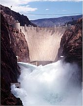 Front view of a dam in a narrow canyon, with water shooting out of the gates