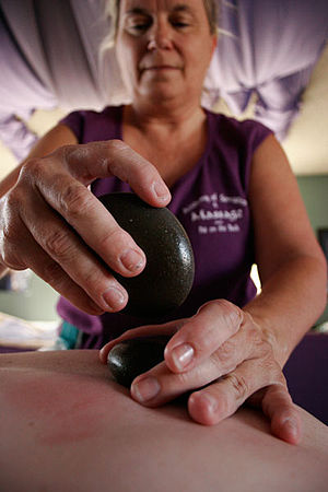 De Etta Sanchez performs a hot stone massage a...