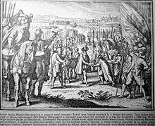 Мужчина в большой шляпе встречает другого мужчину, оба окружены большой толпой вооруженных людей.