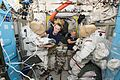 ISS-48 Kate Rubins and Jeff Williams outfit spacesuits inside the Quest airlock.jpg
