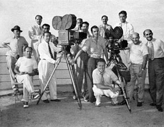It's All True (film) - Some of Welles's film crew at the top of Sugarloaf Mountain, Rio de Janeiro, in early 1942. Standing, from left: John M. Gustafson, Technicolor technician; Dante Orgolini, Mercury public relations; Jose Santos (perhaps Orlando Santos, assistant from the Cinédia studio); Duke Greene, Technicolor cinematographer;  Sidney Zisper, Technicolor technician; Henry Imus, Technicolor camera operator; Ned Scott, still photographer; Joseph Biroc, camera operator (black-and-white); Robert Meltzer, screenwriter and second unit director; Willard Barth, assistant cameraman; Leo Reiser, location production coordinator. Seated at left: James Curley, grip. Crouching: Harry J. Wild, cinematographer (black-and-white).