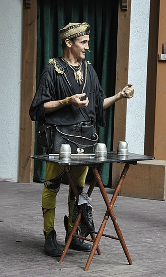 Cups and balls - Johnny Fox performing cups and balls routine at Maryland Renaissance Festival. A gibeciere can be seen around his waist.