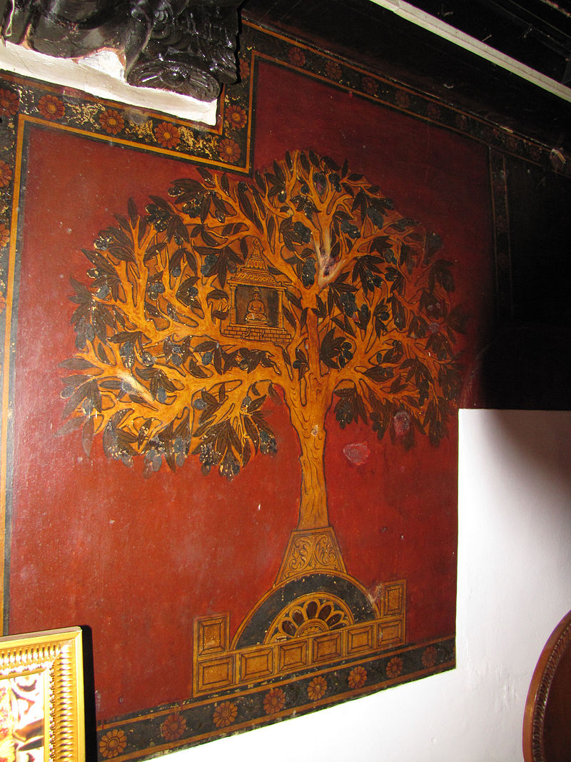 Artisitc representation of the Kalpavriksha in Jainism. A wall painting of a tree on red backdrop.