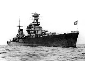 Water-level bow view of a large grey ship flying the Soviet Naval Ensign. Two gun turrets and the forward superstructure are prominent.
