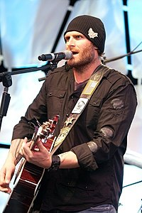 Kyle Turley playing guitar and singing with a black shirt and black hat.jpg