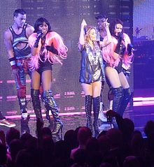 A woman in a sparkly vest is flanked by two background singers in black leotards with pink wigs as shoulder pads. All in the photo are singing into microphones.