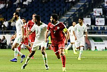 Hassan Maatouk and a Saudi player running while looking in the same direction