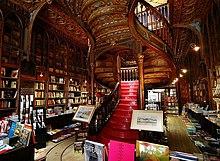 Intérieur d'une librairie comportant un grand escalier central et torsadé en bois foncé sculpté et aux marches rouge vif. Les livres recouvrent les murs tout autour, sur des étagères faites du même bois