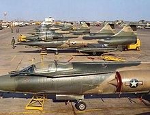 Row of numerous F-104 aircraft parked on display on airport apron