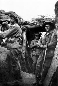 A black and white photograph of men wearing military units in a trench. One man stands on a parapet looking away to the left, while others behind him stare into the camera