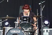 Um baterista fêmea, Lori Barbero, sentado atrás de uma drumkit, em um cenário de desempenho.