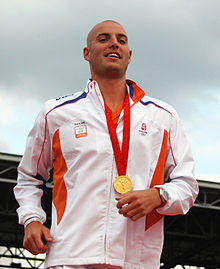 Shaven headed man with a gold medal hung around his neck on a red ribbon, wearing a watch on his left hand and a white tracksuit with small pieces of blue and orange.