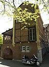 foto van Huis met geblokte kruis- en tweelichtvensters van Naamse steen en een hoofdgestel met consoles van mergel.