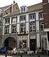 foto van Huis met lijstgevel, voorzien van vensters in Naamse steen en met een rondbogige koetspoort.