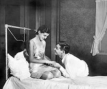 A young woman in a slip dress is kneeling on a bed while smiling at the young man clasping her hands, who is laying in a prone position in a dress shirt and pants and is smiling back.