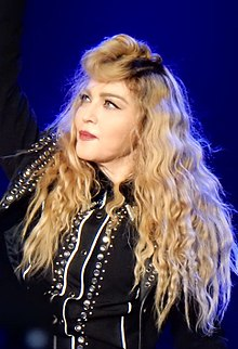 8b0a465ffe72 Madonna in a bejeweled jacket with blond hair in curls around her looking  towards her right