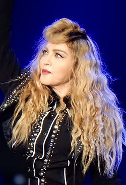 Madonna in a bejeweled jacket with blond hair in curls around her looking towards her right.