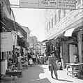 Man slaat een hand voor zijn gezicht al lopend op een markt in de straten van Me, Bestanddeelnr 255-2474.jpg