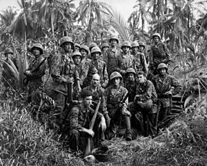 Jungle warfare - U.S. Marine Raiders gathered in front of a Japanese dugout on Cape Totkina on Bougainville, Solomon Islands.