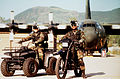 Master Sgt. Enoch Johnson sits on a motorcycle, and Airman 1st Class Joe Youdell sits on the four-wheeler in front of a parked C-130 Hercules 960601-F-09345-002.jpg