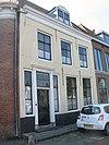 foto van Huis met gepleisterde lijstgevel waarboven dakkapel met segmentboog en zijwangen