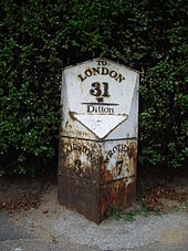 A photograph showing a small monument at the roadside. The bottom of the white cast-iron monument is v-shaped towards the road. The right hand side reads 'WROTHAM 7' and the left reads 'MAIDSTONE 3'. There is rust damage to its base. On the head of the monument, parallel to the road, the legend, in black-painted relief, reads 'To LONDON 31'