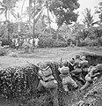 Militairen in een greppel houden hun wapens gericht op een langslopende groep I, Bestanddeelnr 15810.jpg