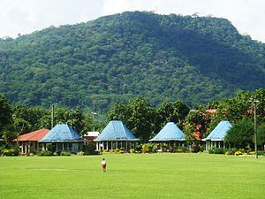 Lepea - Round Samoan meeting houses (fale tele) with blue painted roofs in Lepea village with Mount Vaea beyond, the burial place of Robert Louis Stevenson.