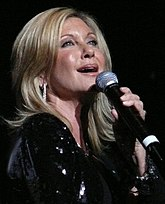A woman with blond hair in black clothing, holding a microphone