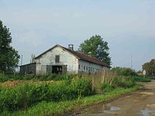 View of a long red-roofed farm building surrounded by overgrown ground at the side of a muddy road