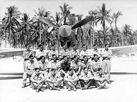 Three rows of men in tropical uniform posing before a single-engined P-40 Kittyhawk fighter plane, with palm trees in the background