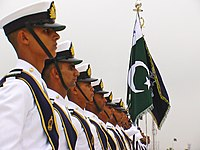 Pakistan Navy soldiers in a straight line are standing next to their national flag.
