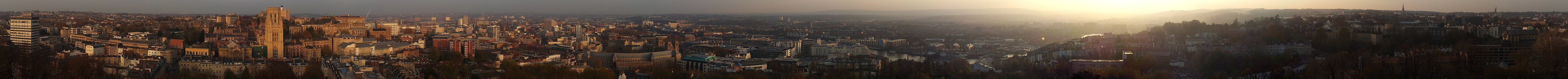 A photographic panorama of Bristol taken from the top of the Cabot Tower. The picture shows an urban environment with densely packed offices and older buildings. Hills can be seen in the distance.