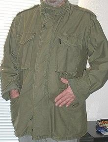 6e4205e5 En olivengrøn fritidsjakke eller parkas i militærstil, med lommer og  skulderklapper.